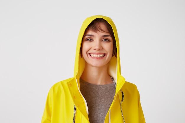 白い壁の上に立って、広く笑顔で、黄色のレインコートを着た若い魅力的な幸せな女の子のクローズアップ。一日を楽しんでいます。ポジティブな感情の概念。