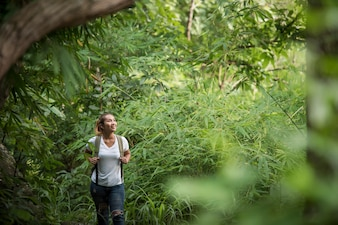Close up of young backpacker walking through the forest happy with nature.