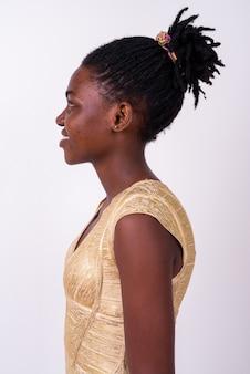 孤立したパーティーの準備ができて金のドレスを着て若い美しいアフリカの女性のクローズアップ