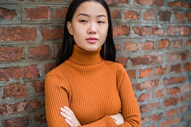 Закройте вверх молодой красивой азиатской женщины смотря уверенно и стоящей против космоса кирпичной стены.