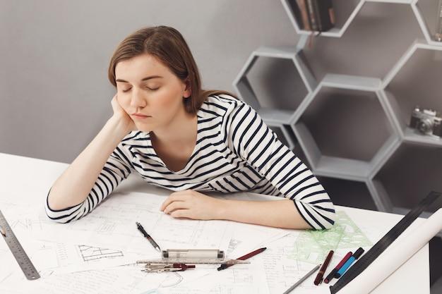 Закройте вверх молодой красивой сонной независимой девушки архитектора держа голову с рукой, падая уснувший пока подготавливающ бумаги для встречи с командой для того чтобы поговорить о деталях проекта.