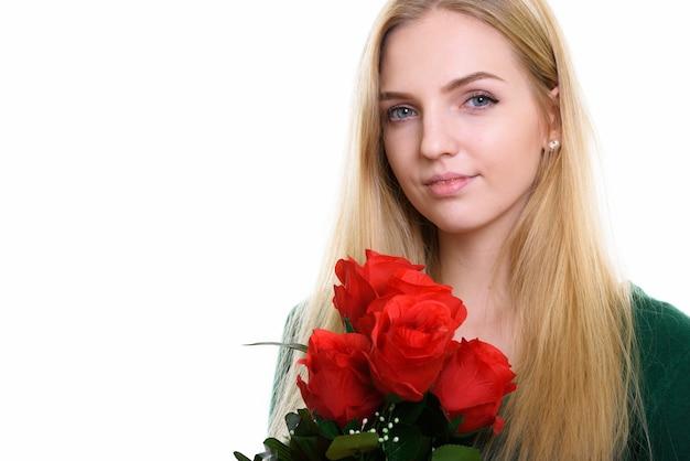 赤いバラの準備ができて保持している若い美しい10代の少女のクローズアップ