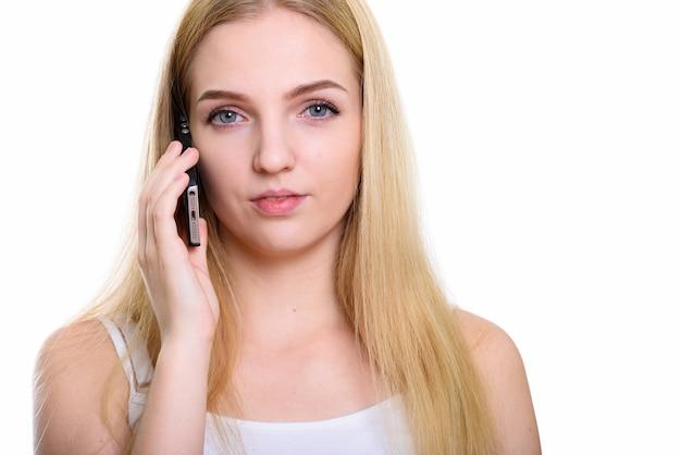 携帯電話で話している若い美しい10代の女性のクローズアップ