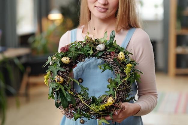 꽃에서 만든 화환을 들고 있는 아름다운 젊은 여성의 클로즈업