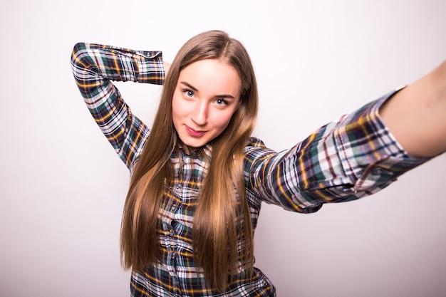 自撮りをしている若い美しい女性のクローズアップ。孤立した白い壁