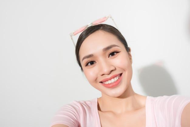 Selfie를 복용하는 젊은 아름 다운 여자의 클로즈업입니다. 격리 된 흰 벽