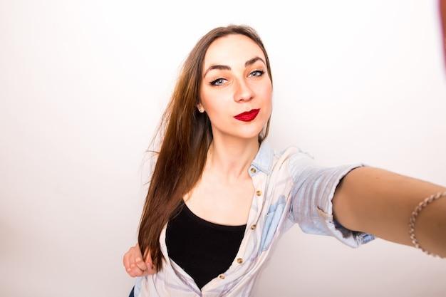 自撮りをしている若い美しい女性のクローズアップ。孤立した白
