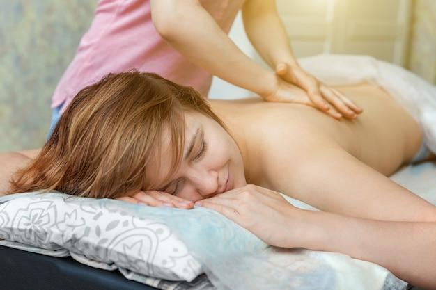 스파 살롱에서 몸을 다시 마사지 치료를 받고 젊은 아름다움 갈색 머리 여자의 근접
