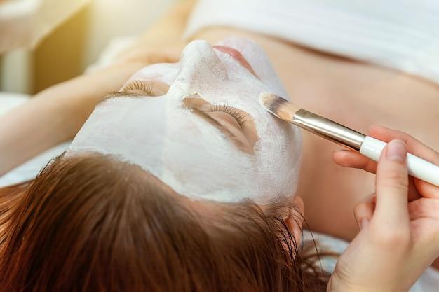 스파 살롱에서 흰색 영양 크림으로 얼굴 치료를 받고 있는 젊은 미인 브루네트 여성의 클로즈업. 얼굴 마사지. 스파 스킨 및 바디 케어. 스킨케어 클렌징 코스메틱 스파 릴랙스 컨셉