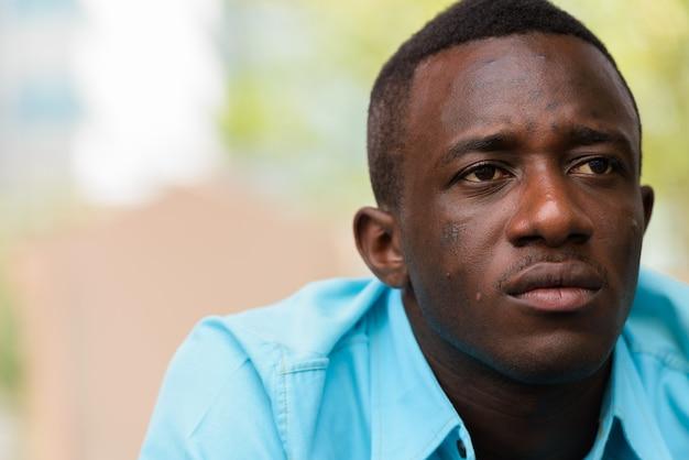 外で考えながら座っている若い黒人アフリカ人のクローズアップ