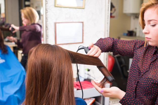 バックグラウンドで大きな鏡のぼやけた反射とサロンで女性ブルネットクライアントの長い髪にフラットアイロンを使用して若いブロンドのスタイリストのクローズアップ