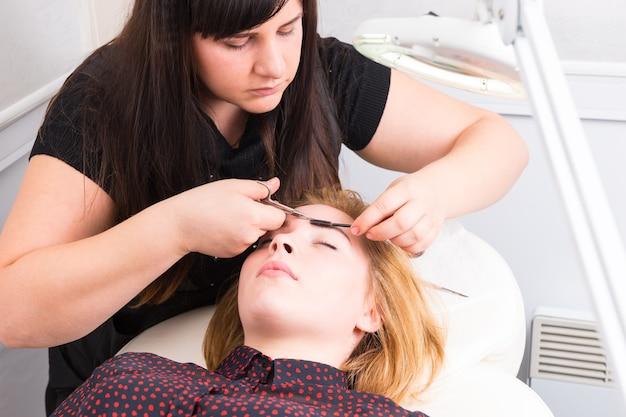 Крупным планом молодой блондинки, лежащей с закрытыми глазами и бровей, подстриженных косметологом с помощью ножниц и кисти для туши в салоне спа