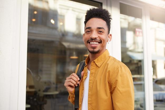 通りを歩いて陽気に見える黄色いシャツを着た若い広く笑顔の暗い肌の男のクローズアップ、ヘッドフォンでお気に入りの曲を聴きながら、街の晴れた日を楽しんでください。