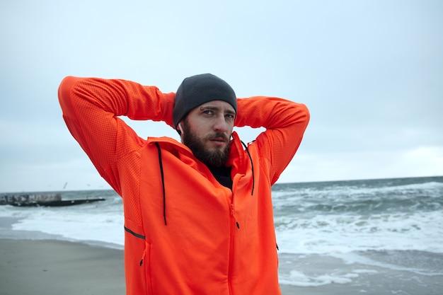 黒の帽子と暖かいオレンジ色のコートを着た若いブルネットのひげを生やしたスポーツマンのクローズアップは、灰色の荒天で海辺の上に立って、朝のランニングセッションの後に景色を楽しんでいます
