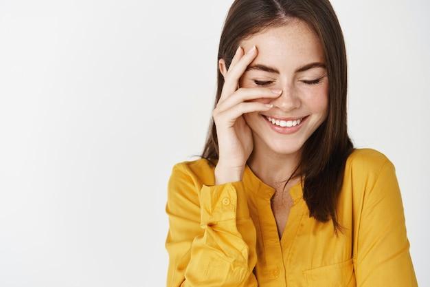 Крупный план молодой брюнетки, улыбающейся счастливой, касающейся идеального лица без макияжа и смеющейся с закрытыми глазами, стоящей на белой стене