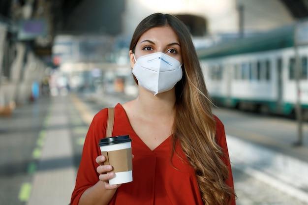 コロナウイルスのパンデミック中に仕事に行くために電車や地下鉄を待っているフェイスマスクを持つ若いビジネス女性のクローズアップ
