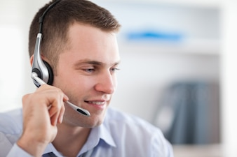 Close up of young call center agent talking with costumer
