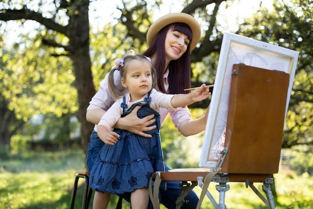 Крупным планом молодой очаровательной матери с ее маленькой дочерью, носить джинсовую одежду, вместе рисовать на мольберте на открытом воздухе в ярком летнем саду. концепция дня матери.