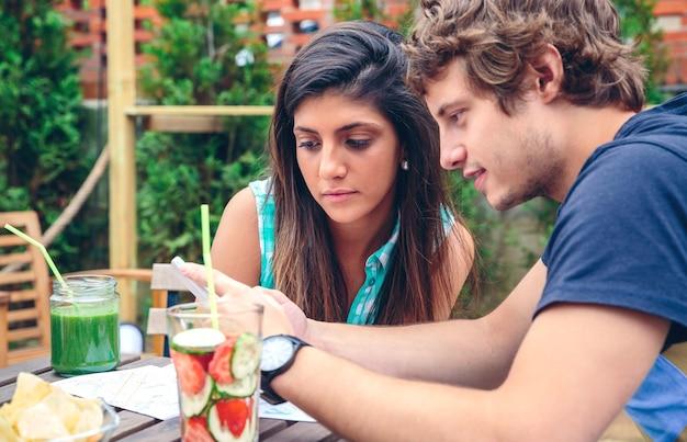 屋外の夏の日に健康的な飲み物とテーブルの周りに座っているスマートフォンを探している若いカップルのクローズアップ