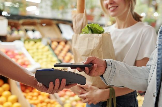 有機食品市場でスマートフォンで新鮮な製品を支払う若いカップルのクローズアップ