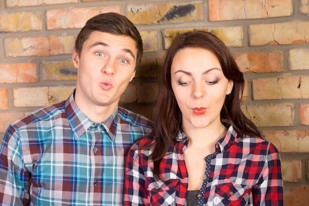 若いカップルの唇をパッカーとレンガの壁の前に立っているのクローズアップ Premium写真