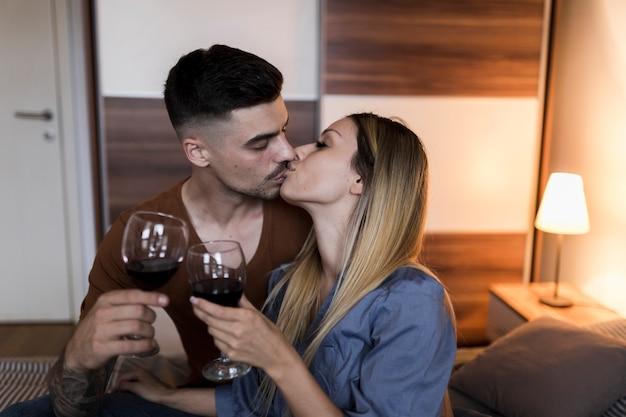 お互いにキスをするワイングラスを焼く若いカップルのクローズアップ