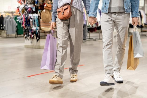 衣料品店を歩きながら手をつないで買い物袋を持つ若いカップルのクローズアップ