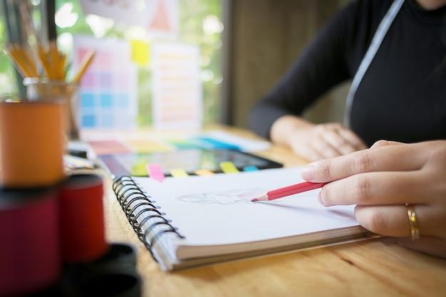 Крупный план молодой креативный модельер, работающий над проектом в современном домашнем офисе