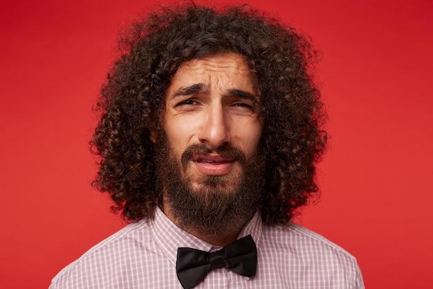 不満を抱いている若いブルネットの巻き毛のひげを生やした男性のクローズアップは、市松模様のシャツと黒の蝶ネクタイを身に着けて立っている間、顔をしかめっ面