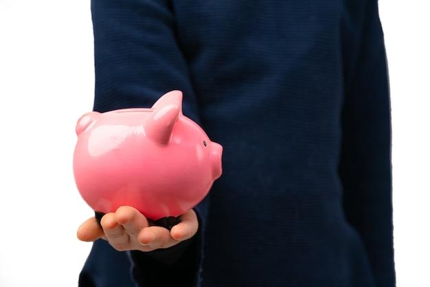 Закройте вверх молодого предпринимателя, держащего копилку. финансовое образование для детей.