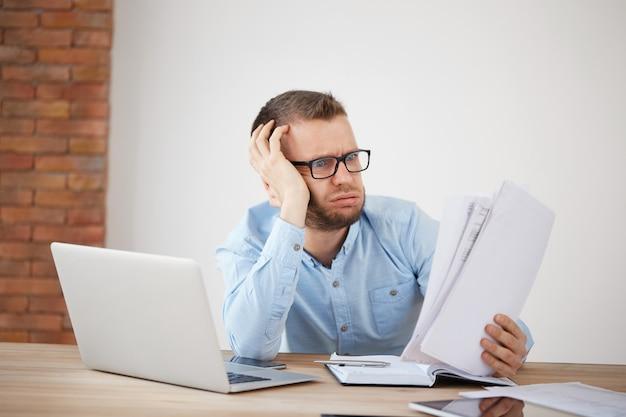 夜遅くまでオフィスに座っている若い疲れて不幸なひげを生やした男性財務マネージャーのクローズアップ