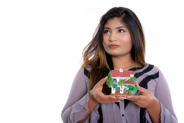 Крупным планом молодая толстая персидская бизнес-леди думает, держа в руках мини-дом