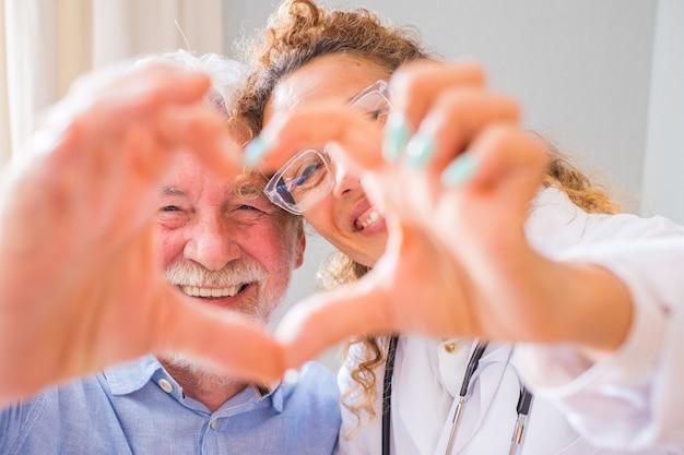 自宅で手でハートサインを示す若い女性医師と年配の男性のクローズアップ。高齢の患者を助け、世話をする医師。高齢者医療。