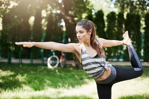 Крупным планом молодая женщина, делающая дандаямана дханурасана в городском парке, расслабляющая стремление к идеальному телу. концепция наружной йоги.