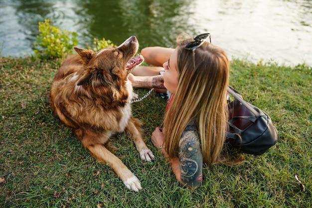 Крупным планом молодой женщины с ее собакой, сидя на траве в парке