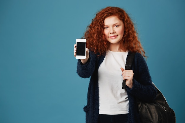 Закройте вверх молодой женщины студента имбиря с волнистыми волосами и веснушками нося белую футболку и черный кардиган показывая smartphone.