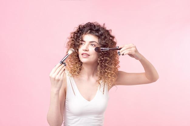 赤面および蛍光ペンパウダーを適用するための彼女の手に2つのブラシを保持している若い女の子の顔のクローズアップ。