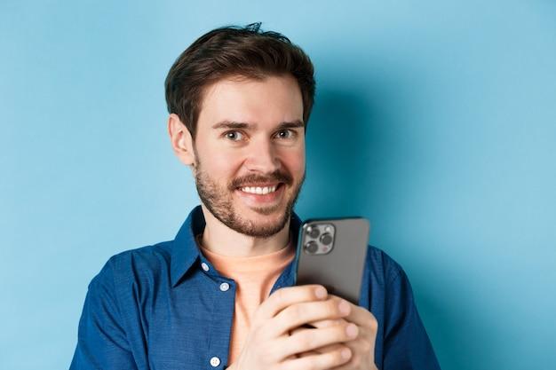 Закройте молодого парня с бородой, улыбаясь счастливой в камеру и держа мобильный телефон, стоя на синем фоне.