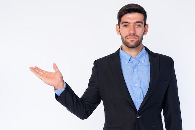孤立したスーツの若いハンサムなひげを生やしたペルシャの実業家のクローズアップ