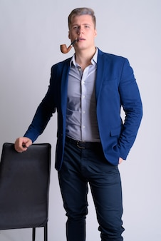 Крупным планом молодой красивый белокурый бизнесмен в изолированном костюме