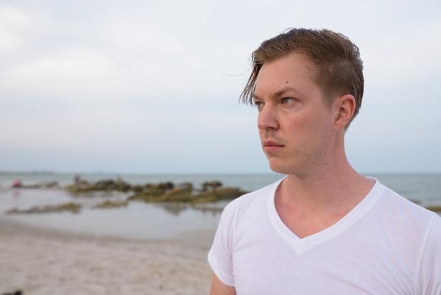 Крупным планом молодой красивый мужчина думает на общественном пляже