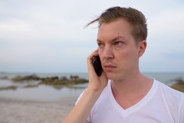 Крупным планом молодой красивый мужчина думает во время разговора по мобильному телефону