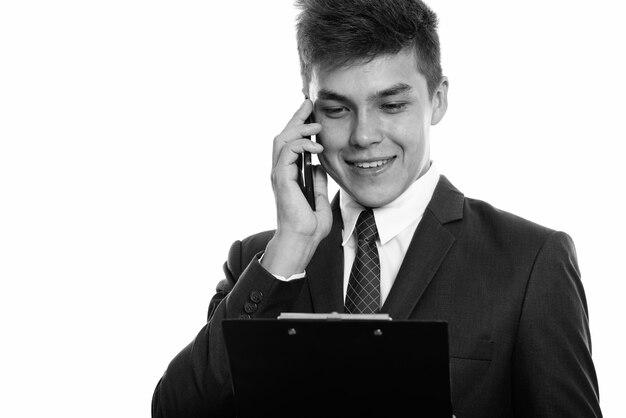 携帯電話で話したり、クリップボードを読んだりしながら笑っている幸せな青年実業家のクローズ アップ