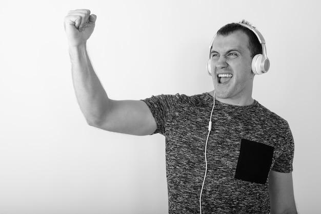 동기를 찾고 음악을 듣는 동안 웃 고 젊은 행복 근육 남자의 닫습니다