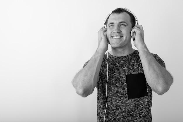 생각하고 음악을 듣는 동안 웃고 젊은 행복 근육질 남자의 닫습니다