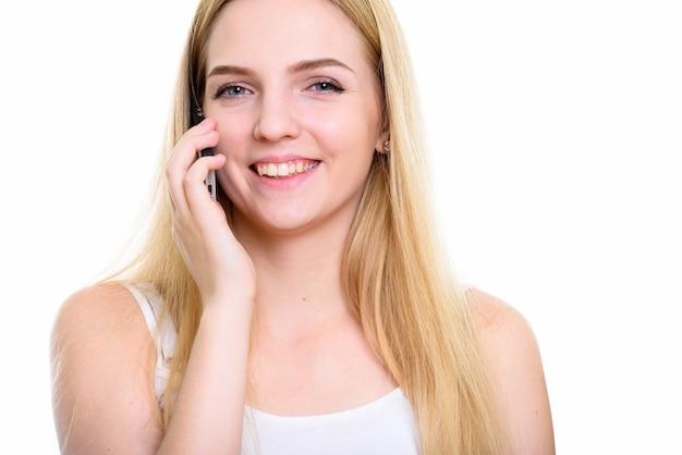 電話で話している間笑顔の若い幸せな10代の女性のクローズアップ