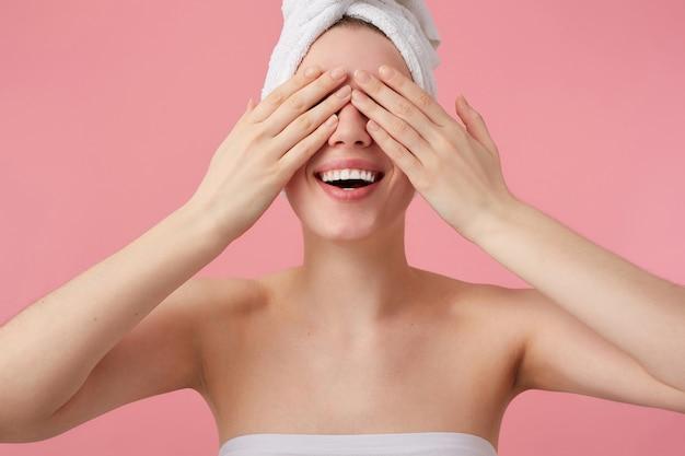 Крупным планом молодая счастливая женщина после душа с полотенцем на голове, широко улыбаясь и закрывая глаза руками, стоит.