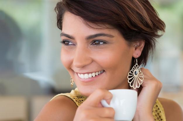 Coffeshopで一杯のコーヒーを保持している若い幸せな女のクローズアップ