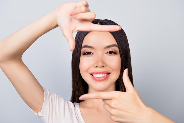 フレームの指を作る若い幸せな女性のクローズアップ
