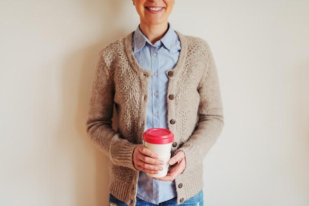 一杯のコーヒーを保持している流行に敏感な若い女性の手のクローズアップ。壁に立っている女の子。